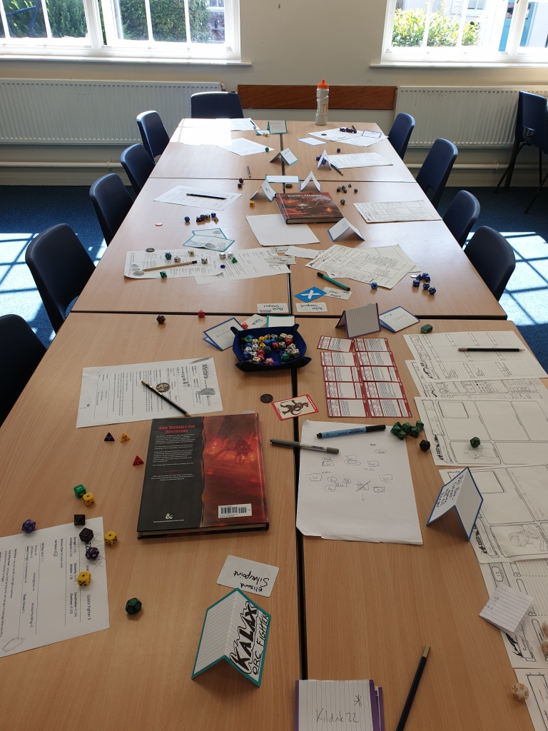 An empty game table with lots of dice, notes, character sheets, card names, and D&D books